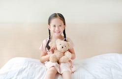 Λατρευτό λίγο ασιατικό παιχνίδι κοριτσιών teddy αντέχει καθμένος στο κρεβάτι στο σπίτι στοκ εικόνα