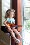 Λατρευτό λίγο ξανθό κορίτσι μικρών παιδιών σγουρός-τρίχας καυκάσιο με τα μπλε μάτια κρατά μια κιθάρα ukulele, καθμένος στην υψηλή στοκ εικόνα