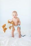 Λατρευτό μικρό αγοράκι που στέκεται στο κρεβάτι και που κρατά το στηθοσκόπιο με τη teddy αρκούδα Στοκ Εικόνες