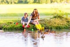 Λατρευτό μικρό κορίτσι και το mom της που παίζουν με τις βάρκες εγγράφου σε ένα ρ Στοκ Εικόνες