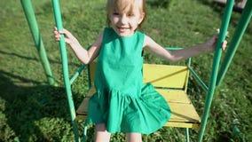 Λατρευτό μικρό κορίτσι που έχει τη διασκέδαση σε μια ταλάντευση υπαίθρια φιλμ μικρού μήκους