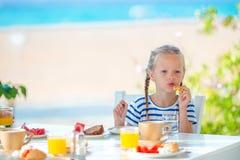 Λατρευτό μικρό κορίτσι που έχει το πρόγευμα στον καφέ με την άποψη θάλασσας νωρίς το πρωί Στοκ εικόνα με δικαίωμα ελεύθερης χρήσης