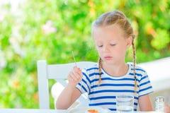 Λατρευτό μικρό κορίτσι που έχει το πρόγευμα στον καφέ με την άποψη θάλασσας νωρίς το πρωί Στοκ Εικόνα