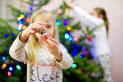 Λατρευτό μικρό κορίτσι που διακοσμεί το χριστουγεννιάτικο δέντρο με τα ζωηρόχρωμα μπιχλιμπίδια γυαλιού Τακτοποίηση του χριστουγεν Στοκ φωτογραφία με δικαίωμα ελεύθερης χρήσης