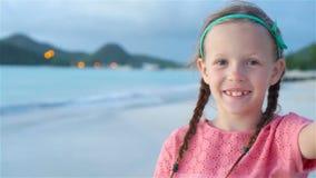 Λατρευτό μικρό κορίτσι που κάνει selfie στην τροπική άσπρη παραλία κίνηση αργή απόθεμα βίντεο
