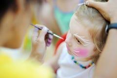 Λατρευτό κορίτσι που παίρνει το πρόσωπό της χρωματισμένο Στοκ Φωτογραφίες