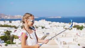 Λατρευτό μικρό κορίτσι που παίρνει selfie την πόλη της Μυκόνου υποβάθρου φωτογραφιών στην Ελλάδα φιλμ μικρού μήκους