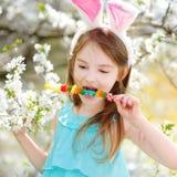 Λατρευτό μικρό κορίτσι που τρώει τις ζωηρόχρωμες καραμέλες γόμμας σε Πάσχα Στοκ Εικόνες