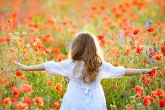 Λατρευτό μικρό κορίτσι που φορά το άσπρο φόρεμα στο θερινό ανθίζοντας τομέα στοκ εικόνες
