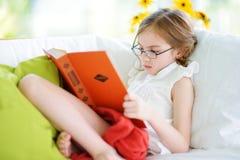 Λατρευτό μικρό κορίτσι που φορά eyeglasses που διαβάζουν ένα βιβλίο στο άσπρο καθιστικό Στοκ εικόνα με δικαίωμα ελεύθερης χρήσης