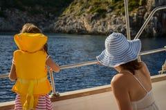 Λατρευτό μικρό κορίτσι σε ένα σακάκι ζωής που ταξιδεύει στη βάρκα με τη μητέρα της Στοκ Εικόνα