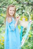 Λατρευτό μικρό κορίτσι στον ανθίζοντας κήπο μήλων την όμορφη ημέρα άνοιξη Στοκ Φωτογραφία