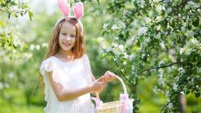 Λατρευτό μικρό κορίτσι στον ανθίζοντας κήπο μήλων την όμορφη ημέρα άνοιξη απόθεμα βίντεο