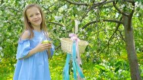 Λατρευτό μικρό κορίτσι στον ανθίζοντας κήπο μήλων την όμορφη ημέρα άνοιξη φιλμ μικρού μήκους