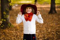 Λατρευτό μικρό κορίτσι στον κόκκινο περίπατο καπέλων στο πάρκο φθινοπώρου στοκ φωτογραφία με δικαίωμα ελεύθερης χρήσης