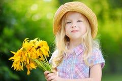 Λατρευτό μικρό κορίτσι στο καπέλο αχύρου που κρατά τα όμορφα κίτρινα λουλούδια Στοκ εικόνα με δικαίωμα ελεύθερης χρήσης
