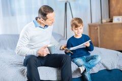 Λατρευτό μικρό παιδί που παρουσιάζει μια εικόνα στον πατέρα του Στοκ Εικόνες