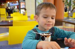 Λατρευτό μικρό παιδί σε ένα επιχειρησιακό κοστούμι επιχειρηματιών ` s σε μια βιασύνη που τρώει το παγωτό στο εστιατόριο κατά τη δ στοκ εικόνα με δικαίωμα ελεύθερης χρήσης