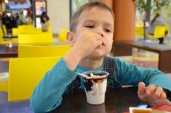 Λατρευτό μικρό παιδί σε ένα επιχειρησιακό κοστούμι επιχειρηματιών ` s σε μια βιασύνη που τρώει το παγωτό στο εστιατόριο κατά τη δ στοκ φωτογραφία με δικαίωμα ελεύθερης χρήσης
