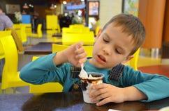 Λατρευτό μικρό παιδί σε ένα επιχειρησιακό κοστούμι επιχειρηματιών ` s σε μια βιασύνη που τρώει το παγωτό στο εστιατόριο κατά τη δ στοκ φωτογραφίες