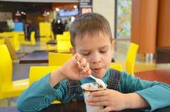 Λατρευτό μικρό παιδί σε ένα επιχειρησιακό κοστούμι επιχειρηματιών ` s σε μια βιασύνη που τρώει το παγωτό στο εστιατόριο κατά τη δ στοκ φωτογραφία