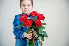 Λατρευτό μικρό παιδί στο κοστούμι με την ανθοδέσμη των κόκκινων τριαντάφυλλων σε ένα ελαφρύ υπόβαθρο στοκ φωτογραφία με δικαίωμα ελεύθερης χρήσης