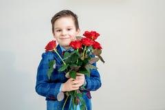 Λατρευτό μικρό παιδί στο κοστούμι με την ανθοδέσμη των κόκκινων τριαντάφυλλων σε ένα ελαφρύ υπόβαθρο στοκ εικόνες με δικαίωμα ελεύθερης χρήσης