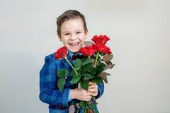 Λατρευτό μικρό παιδί στο κοστούμι με την ανθοδέσμη των κόκκινων τριαντάφυλλων σε ένα ελαφρύ υπόβαθρο στοκ εικόνες