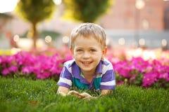 Λατρευτό μικρό παιδί που βρίσκεται μεταξύ των λουλουδιών. Στοκ Εικόνες