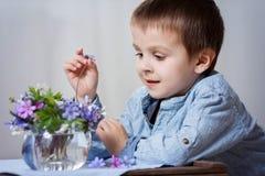 Λατρευτό μικρό παιδί, που εξετάζει το βάζο με την ανθοδέσμη λουλουδιών άνοιξη Στοκ Εικόνα