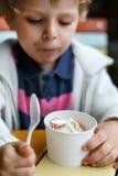 Λατρευτό μικρό παιδί που τρώει το παγωμένο παγωτό γιαουρτιού στον καφέ Στοκ εικόνες με δικαίωμα ελεύθερης χρήσης