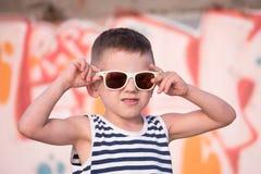 Λατρευτό μικρό παιδί που φορά το πουκάμισο γυαλιών ηλίου και λωρίδων ναυτικών Στοκ εικόνες με δικαίωμα ελεύθερης χρήσης