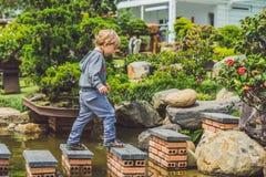 Λατρευτό νέο αγόρι με το πέρασμα του ποταμού ή του νερού που πηδά από το βράχο στο βράχο Πέρασμα του χάσματος, ελευθερία, απελευθ Στοκ Εικόνες