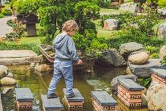 Λατρευτό νέο αγόρι με το πέρασμα του ποταμού ή του νερού που πηδά από το βράχο στο βράχο Πέρασμα του χάσματος, ελευθερία, απελευθ Στοκ Φωτογραφία