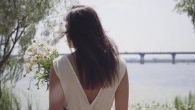 Λατρευτό νέο κορίτσι πορτρέτου με τη μακριά τρίχα brunette που φορά ένα μακρύ άσπρο φόρεμα θερινής μόδας που στέκεται φιλμ μικρού μήκους