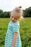 Λατρευτό ξανθό μικρό κορίτσι με το αναιδές χαμόγελο στοκ φωτογραφίες
