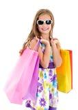Λατρευτό παιδί μικρών κοριτσιών στα γυαλιά ηλίου που κρατά τις αγορές colorf Στοκ φωτογραφία με δικαίωμα ελεύθερης χρήσης