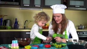 Λατρευτό παιδί που διακοσμεί muffin τα φλυτζάνια Λίγο κορίτσι αρωγών με τη μητέρα απόθεμα βίντεο