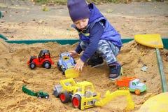 Λατρευτό παιχνίδι αγοράκι σε ένα Sandbox την ημέρα φθινοπώρου Παιχνίδια άμμου σε ένα Sandbox στοκ εικόνες με δικαίωμα ελεύθερης χρήσης