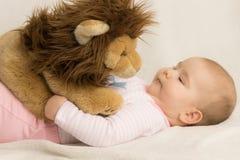 Λατρευτό παιχνίδι κοριτσάκι με ένα παιχνίδι λιονταριών βελούδου Στοκ Εικόνες