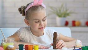Λατρευτό παιχνίδι κοριτσιών με το λαγουδάκι σοκολάτας και χαμόγελο στη κάμερα, παιδική ηλικία απόθεμα βίντεο