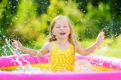 Λατρευτό παιχνίδι μικρών κοριτσιών στη διογκώσιμη λίμνη μωρών Ευτυχές ράντισμα παιδιών στο ζωηρόχρωμο κέντρο παιχνιδιού κήπων την Στοκ εικόνες με δικαίωμα ελεύθερης χρήσης