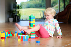 Λατρευτό παιχνίδι κοριτσιών μικρών παιδιών με τα παιχνίδια στο πάτωμα Στοκ Εικόνα