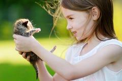 Λατρευτό παιχνίδι μικρών κοριτσιών με το μικρό γατάκι Στοκ Εικόνα