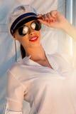 Λατρευτό πρότυπο φορώντας καπέλο ναυάρχων θάλασσας και προκλητική κορυφή στο ηλιοβασίλεμα Στοκ Εικόνες