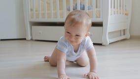 Λατρευτό χαμογελώντας μωρό που σέρνεται στο πάτωμα προς τη κάμερα απόθεμα βίντεο