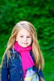 Λατρευτό χαμογελώντας ξανθό μικρό κορίτσι που φορά το ρόδινο μαντίλι Στοκ Εικόνες