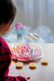 Λατρευτό χαριτωμένο αγόρι, φυσώντας κεριά σε ένα κέικ γενεθλίων Στοκ Φωτογραφία