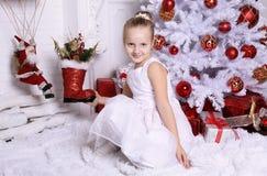Λατρευτό χαριτωμένο κορίτσι με την τοποθέτηση ξανθών μαλλιών εκτός από το χριστουγεννιάτικο δέντρο Στοκ Φωτογραφίες