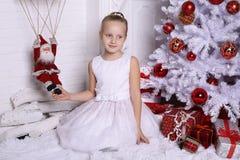 Λατρευτό χαριτωμένο κορίτσι με την τοποθέτηση ξανθών μαλλιών εκτός από το χριστουγεννιάτικο δέντρο Στοκ εικόνες με δικαίωμα ελεύθερης χρήσης